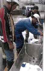 井戸からくみ上げた水をポリタンクに詰める住民たち(勝浦町で)
